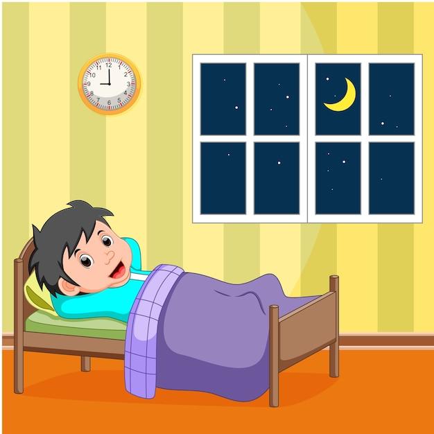 Smile little boy sleeping in the bed | Premium Vector
