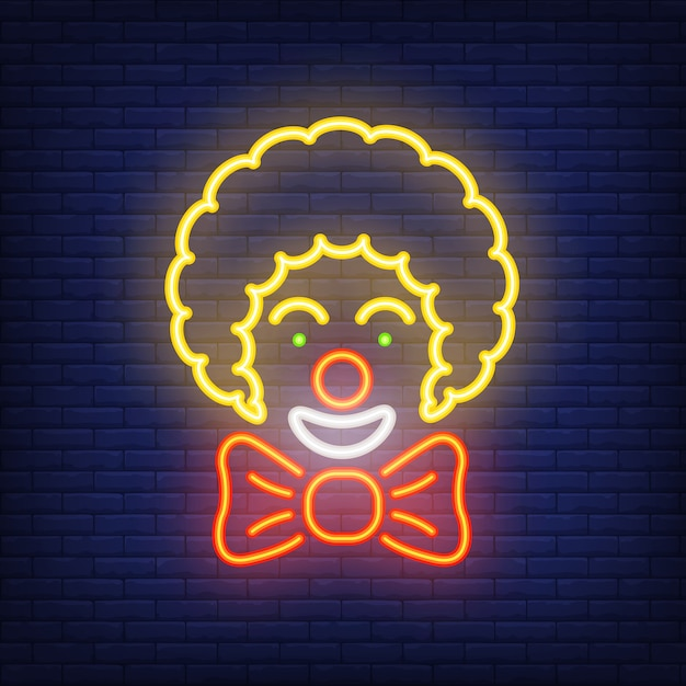 Smiling clown neon icon. circus artist with big bow on dark brick wall background. Free Vector