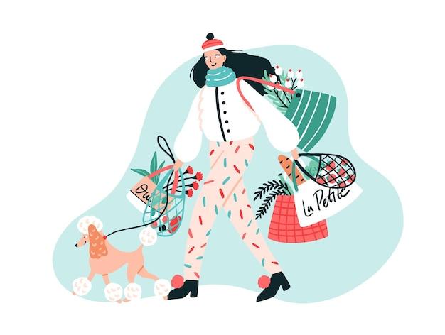 ひもにつないでプードル犬を歩き、購入した製品とバッグを運ぶ流行のアウターウェアに身を包んだ笑顔の若い女性 Premiumベクター