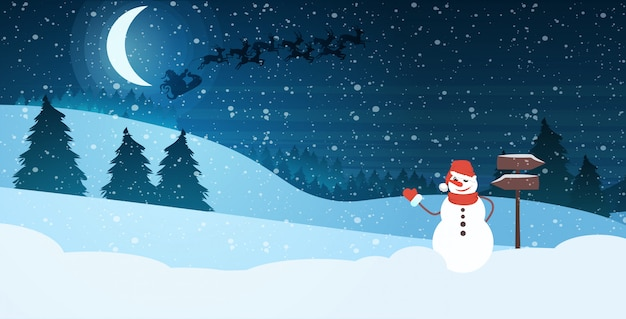 Snowman in hat and scarf waving hand in night pine forest santa flying in sleigh with reindeers in bright starry sky Premium Vector