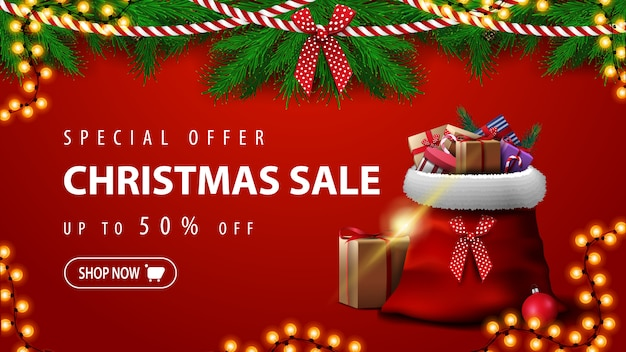 Special offer, christmas sale, up to 50% off, beautiful red discount banner with christmas tree branches, garlands and santa claus bag with presents Premium Vector