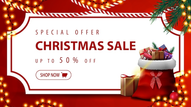 Special offer, christmas sale, up to 50% off, red discount banner with white paper sheet in the form of vintage ticket, christmas tree branches, garlands and santa claus bag with presents Premium Vector