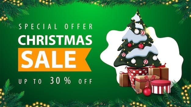 特別オファー、クリスマスセール、最大30%オフ、背景に抽象的な形の緑の割引ウェブバナー、花輪フレーム、クリスマスツリーの枝で作られたフレームとギフト付きのポットにクリスマスツリー Premiumベクター