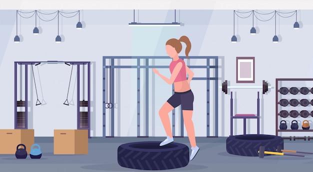 Sporty женщина делать приседания на шинах платформа девушка тренировка ноги тренировка здоровый образ жизни crossfit концепция современный тренажерный зал интерьер горизонтальный плоский Premium векторы