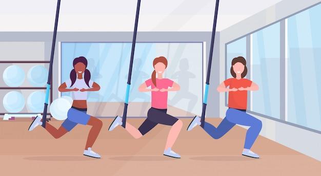 Спортивные женщины, делающие приседания, упражнения с подвеской, фитнес-ремни, эластичная веревка, микс, гонки, тренировка, кроссфит, групповые занятия, тренировка, концепция, современный, тренажерный зал, клуб здоровья, полная длина. Premium векторы