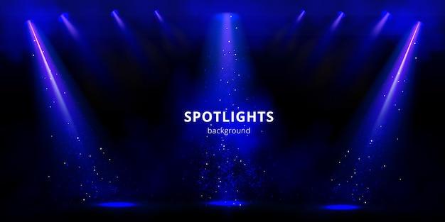 Фон прожекторов, синие сценические световые лучи с дымом и блестками на черном фоне. Бесплатные векторы