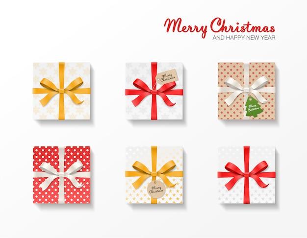 Квадратный подарочный набор. золотой, красный, серебряный цвет банта, ленты, крафт-шар и бирки. снежинка узор, старая бумага. счастливого рождества текст. Premium векторы
