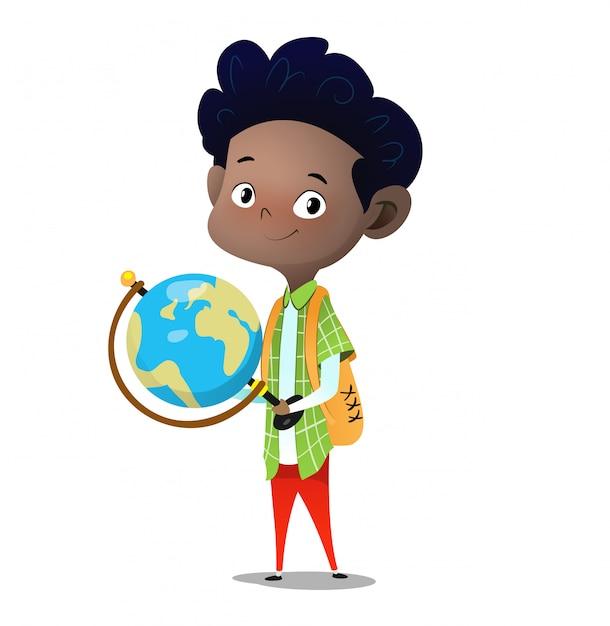 立っている少年が手に大きなデスクトップ地球儀を保持します Premiumベクター