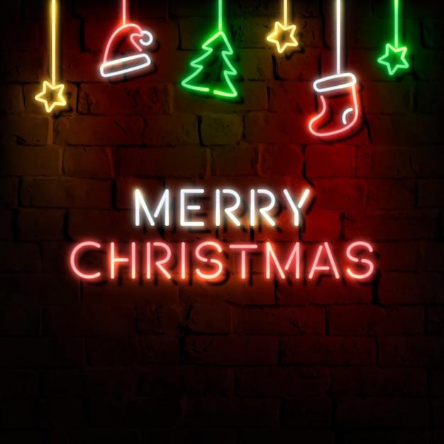 어두운 벽돌 벽에 별, 산타 모자, 스타킹, 소나무 및 메리 크리스마스 네온 사인 무료 벡터