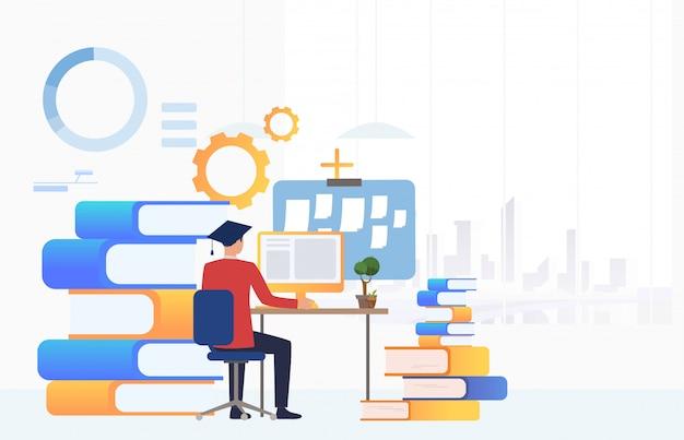 Student in graduation cap using computer at desk Free Vector