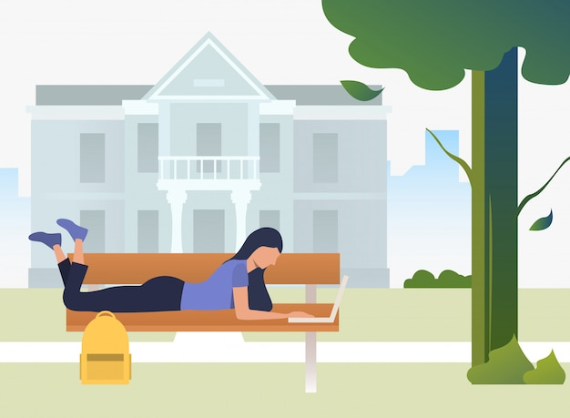 Student studying, using laptop and lying on bench in campus park Free Vector