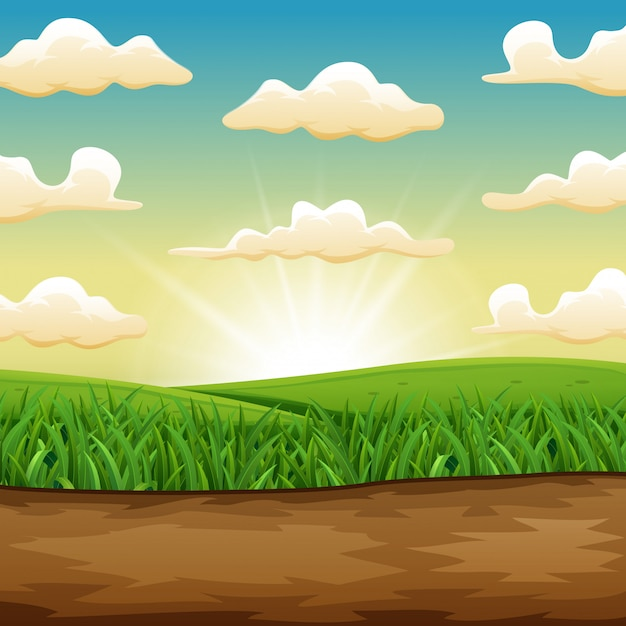 The sun rising or setting over a beautiful green field of grass Premium Vector