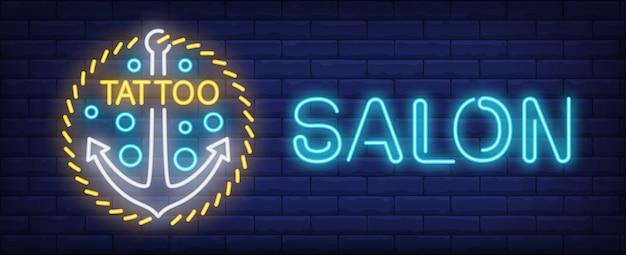 Tattoo salon neon sign. nautical anchor on golden chain. Free Vector
