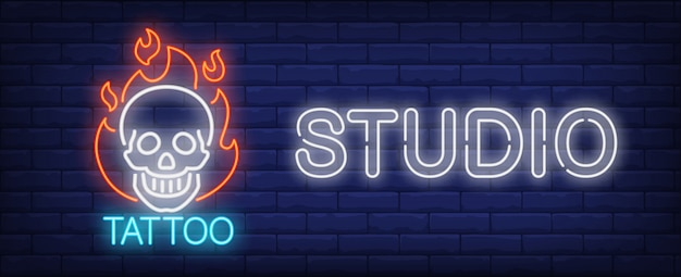 Tattoo studio neon sign. smiling scull on fire and big inscription on dark brick wall. Free Vector