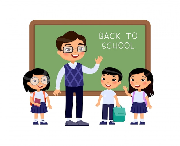 Teacher greeting pupils in classroom flat vector illustration. boys and girls dressed in school uniform and male teacher pointing at blackboard cartoon characters. primary students back to school Free Vector