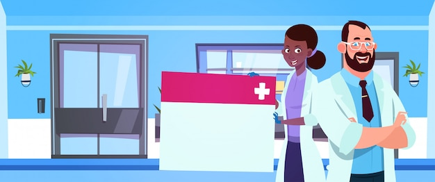 Team of medical doctors holding empty board Premium Vector