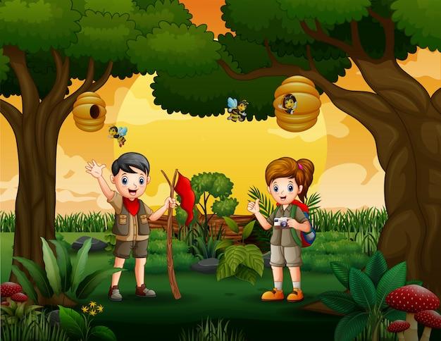 森の中をハイキングする探検家の子供たち Premiumベクター