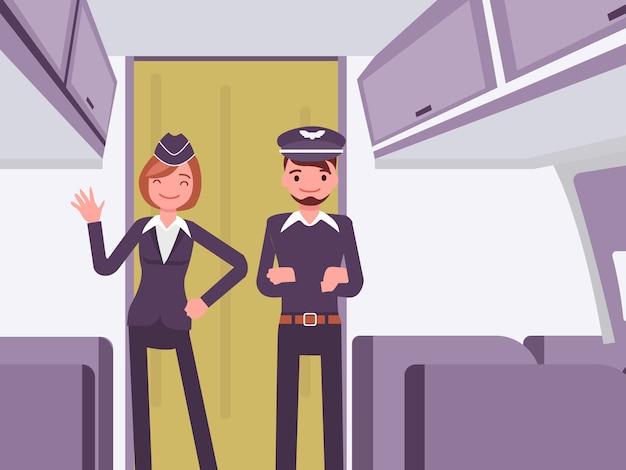 飛行機のキャビンでポーズをとっているパイロットと客室乗務員 Premiumベクター