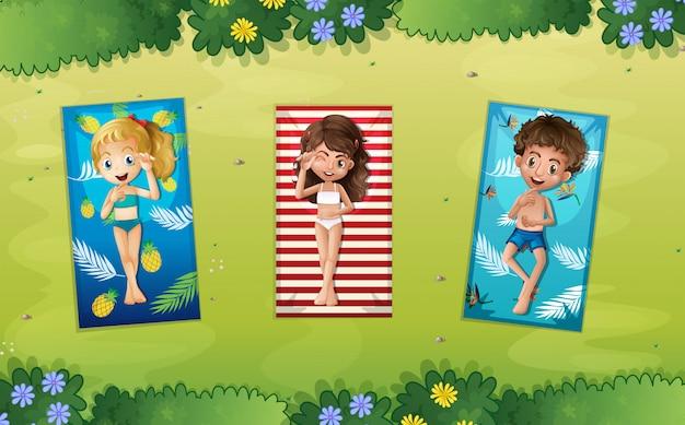 Three children laying in the park Premium Vector