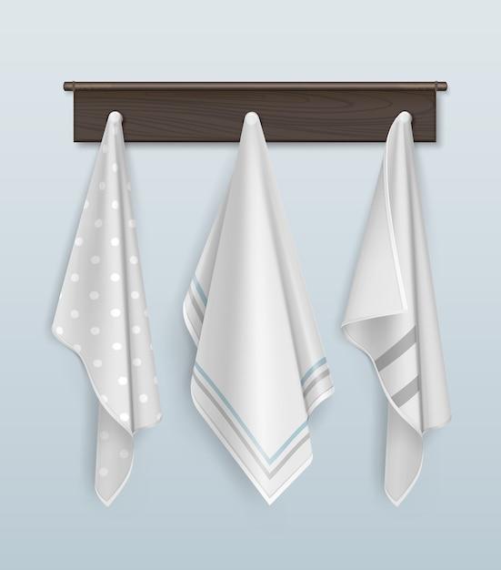 青い壁の茶色の木製のフックにぶら下がっている3つのきれいな綿またはリネンの白と水玉のタオル Premiumベクター
