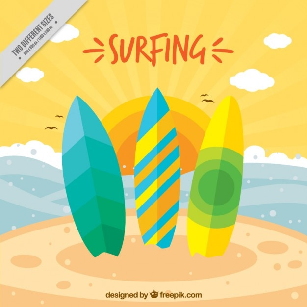 Three colored surfboards on the beach\ background