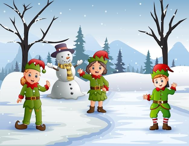 雪に覆われた森で手を振っている3人のエルフ Premiumベクター