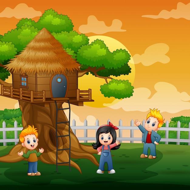 樹上の家の図で遊ぶ3人の子供 Premiumベクター