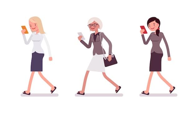 Three women are walking holding a smartphone Premium Vector