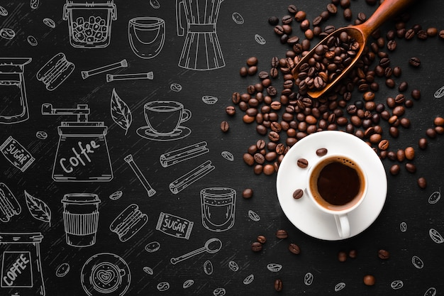 Top view cup of coffee with roasted beans Free Vector