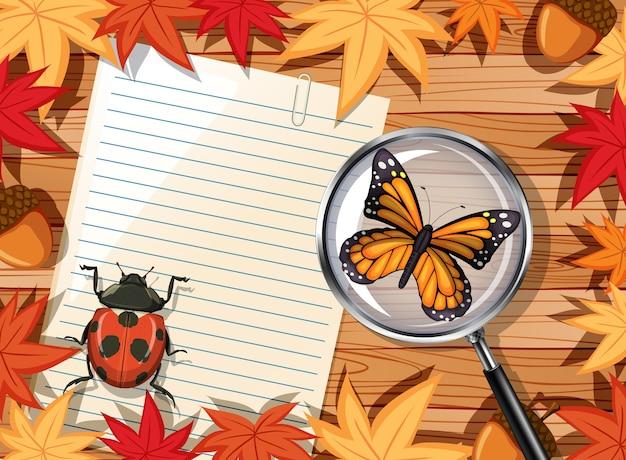 Вид сверху деревянного стола с чистым листом бумаги и элементом насекомых и осенних листьев Premium векторы