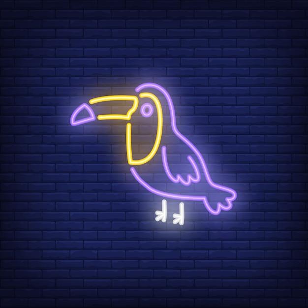 Toucan neon sign. Tropical bird on dark brick\ wall background. Night bright advertisement