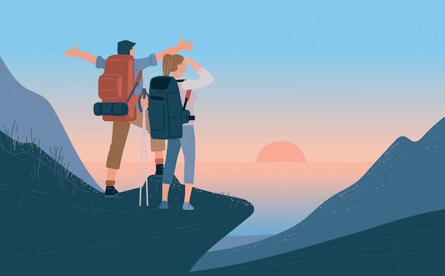 山のバックパックの立っていると海の上の日の出を見ている旅行者の男性と女性 Premiumベクター