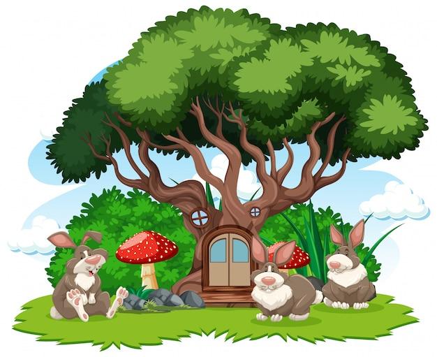 白い背景の上の3つのウサギの漫画のスタイルを持つ木の家 無料ベクター