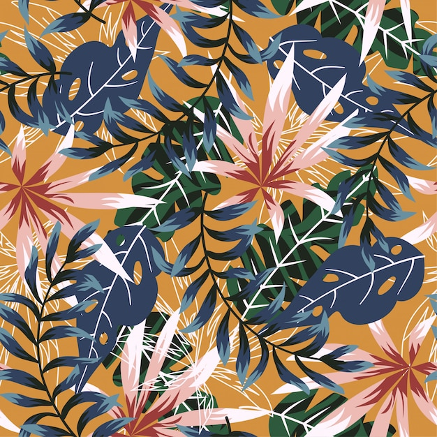 Trend seamless pattern with colorful tropical leaves and plants on orange background Premium Vector