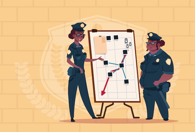 Two african american police women planning action on white board wearing uniform female guards on blue bricks background Premium Vector
