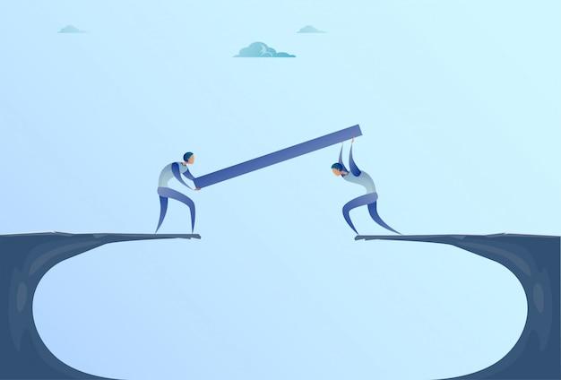 Two businessmen building bridge over cliff gap mountain business people cooperation help teamwork concept Premium Vector