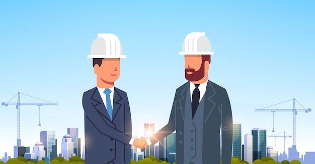 Two businessmen handshaking over city construction site Premium Vector