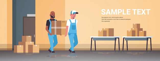 Two couriers in uniform carrying cardboard box package mail express delivery service concept mix race industrial factory workers working in stockroom of storehouse Premium Vector