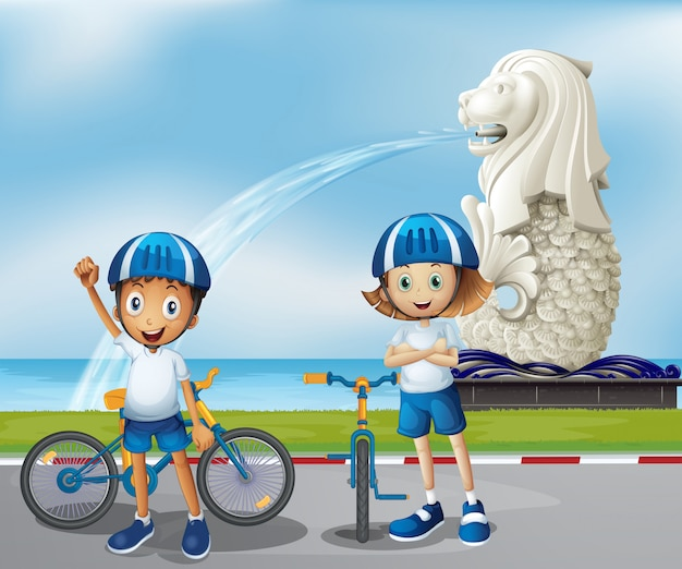 Two cute bikers standing in the front of the merlion Free Vector