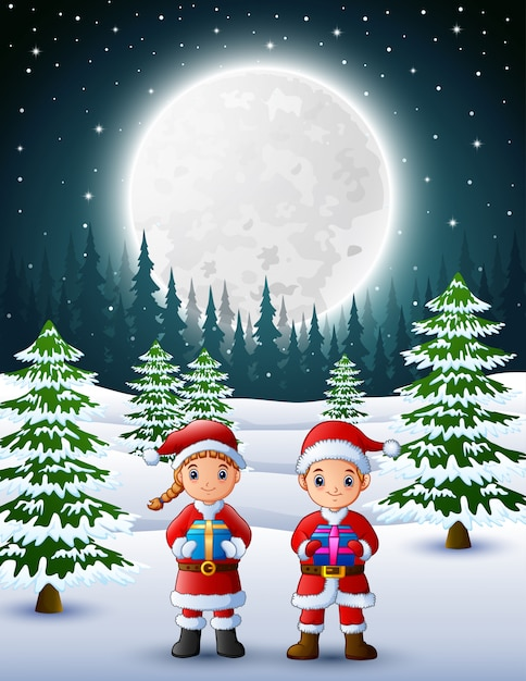 Two kids in santa claus holding a gift box with winter background at ...