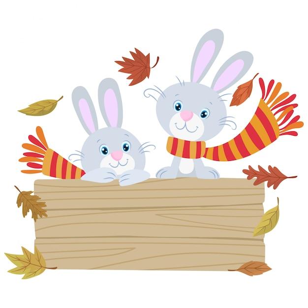 Два маленьких забавных кролика, одетых в шерстяной шарф осенью Premium векторы