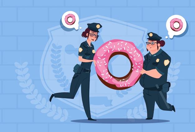Two police women holding donut wearing uniform female guards on blue bricks background Premium Vector