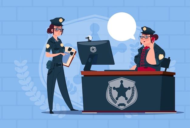 Two police women working on computer wearing uniform female guards on blue bricks background Premium Vector