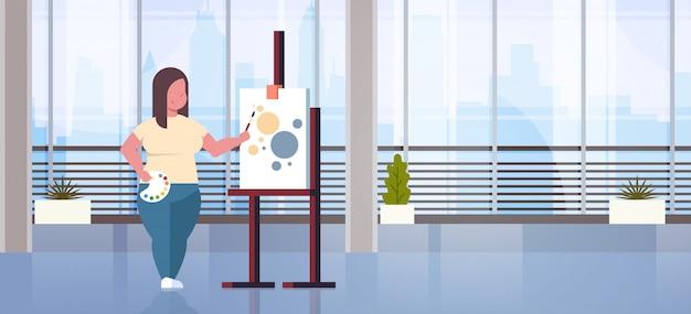 Ты женщина художник держит кисть девушка художник процесс рисования современное искусство мастерская интерьер студии Premium векторы
