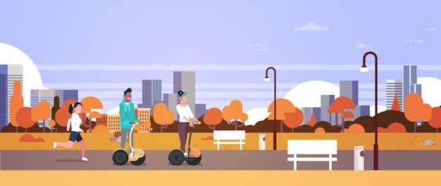 Urban autumn park outdoors activities man woman riding gyroscooter running nature city buildings street lamps cityscape horizontal banner flat Premium Vector
