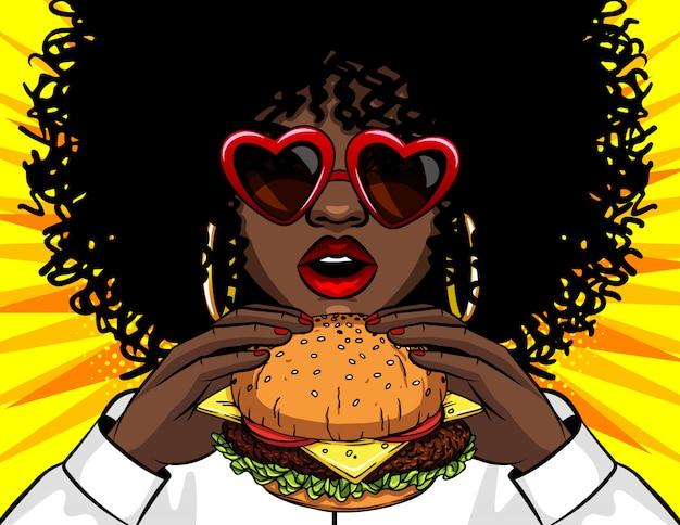 Vector banner african american woman eating a burger. comic cartoon pop art retro vector illustration drawing female hands holding a yummy sandwich Premium Vector
