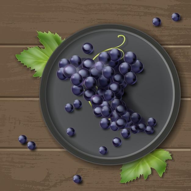 Vector grappolo d'uva sulla piastra con foglie, isolato su sfondo di legno, vista dall'alto Vettore gratuito