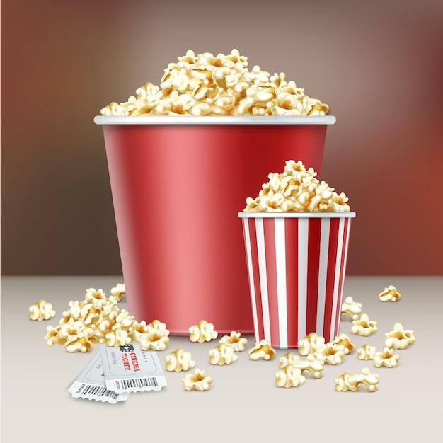 Вектор два белых и красных полосатых ведра ядер попкорна с билетами в кино заделывают вид сбоку на размытом фоне Бесплатные векторы