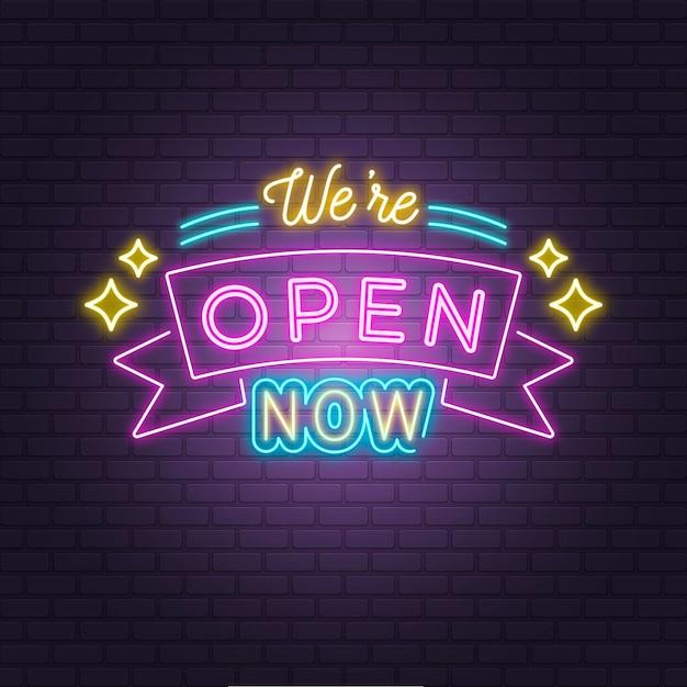 レンガの壁に「私たちは開いています」ネオンサイン 無料ベクター