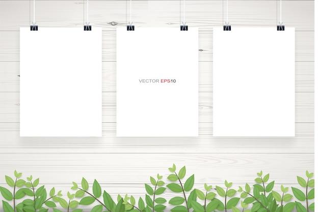 緑の葉のフレームと白い木製の壁のテクスチャの背景にぶら下がっている白い紙のポスター Premiumベクター
